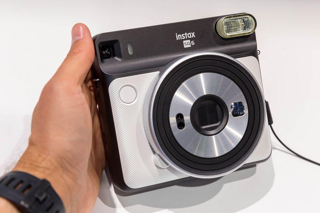 Mann hält Sofortbildkamera Instax Square SQ6 in Pearl White an der Photokina in Köln
