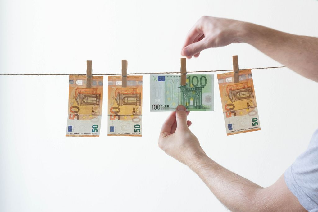 Mann hängt sein Geld an einer Wäscheleine auf