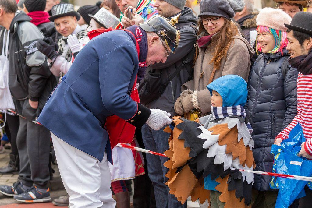 Mann in alter Feuerwehruniform gibt Jungen ein Geschenk - Kölner Karneval 2018