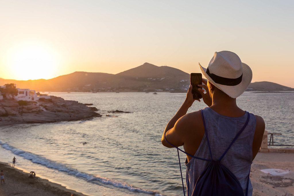Mann macht Handy-Foto vom Sonnenuntergang an der Küste der griechischen Insel Paros