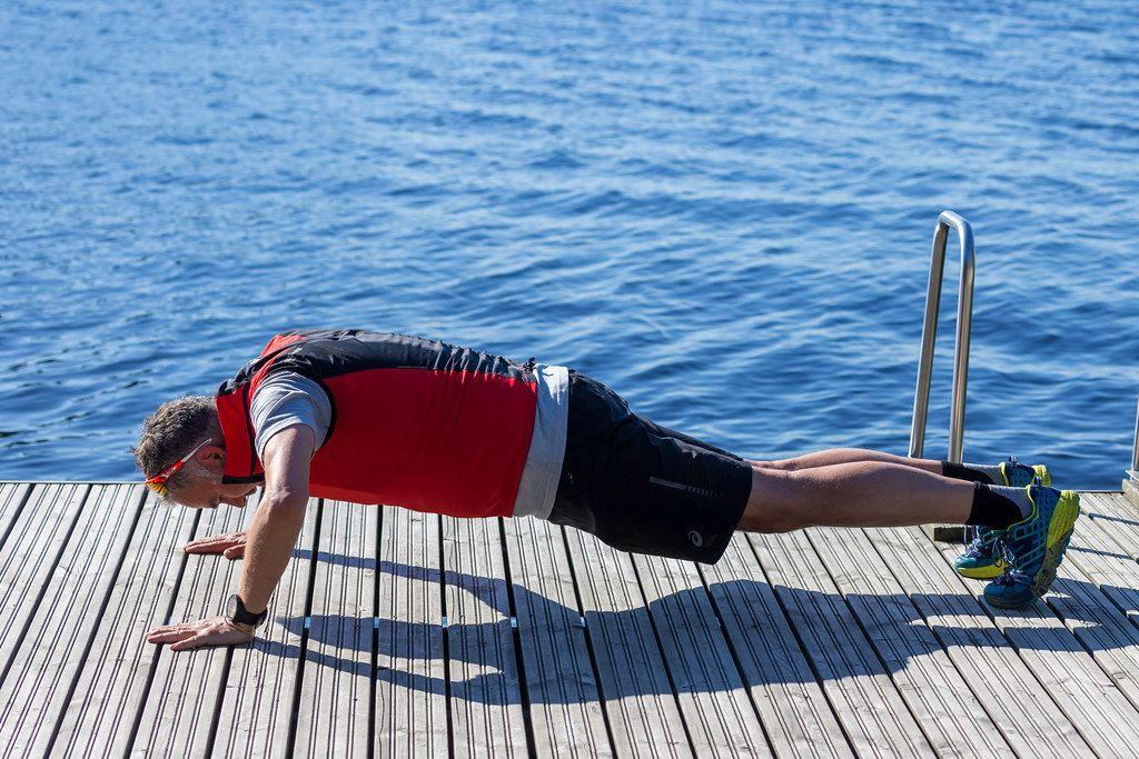 Mann macht Liegestütze während des morgendlichen Work-Outs, auf einem Holzsteg mit blauem Wasser im Hintergrund