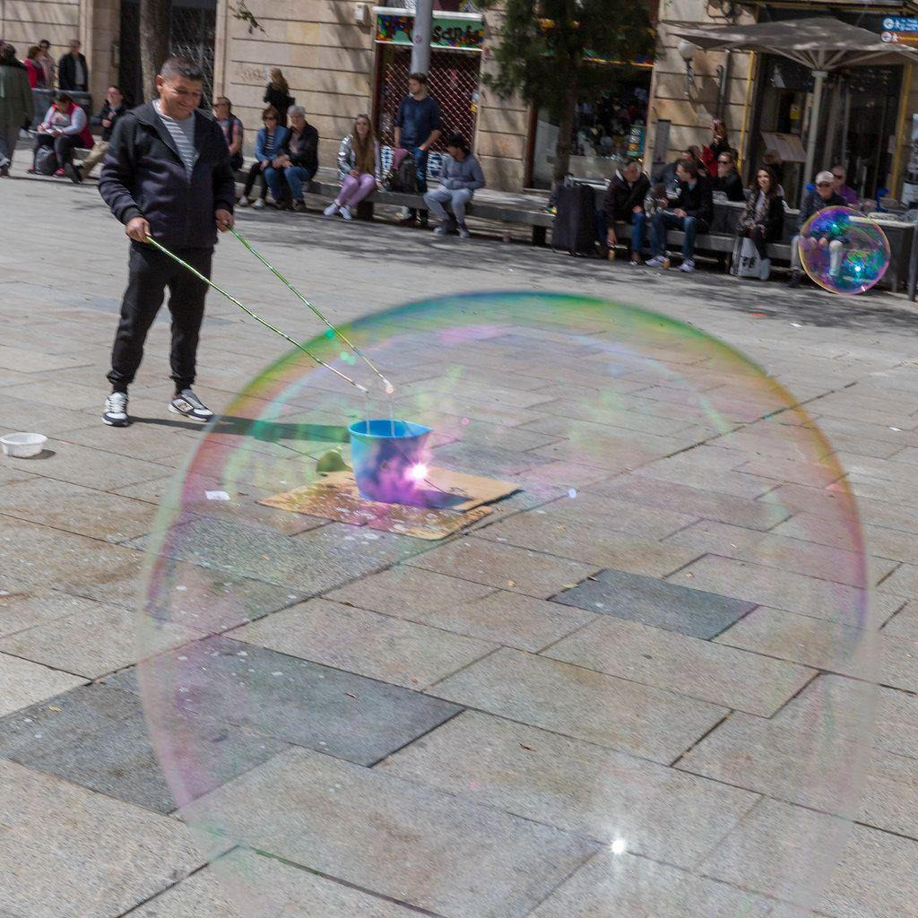 Mann macht riesige bunte Seifenblasen im Zentrum von Barcelona, Katalonien