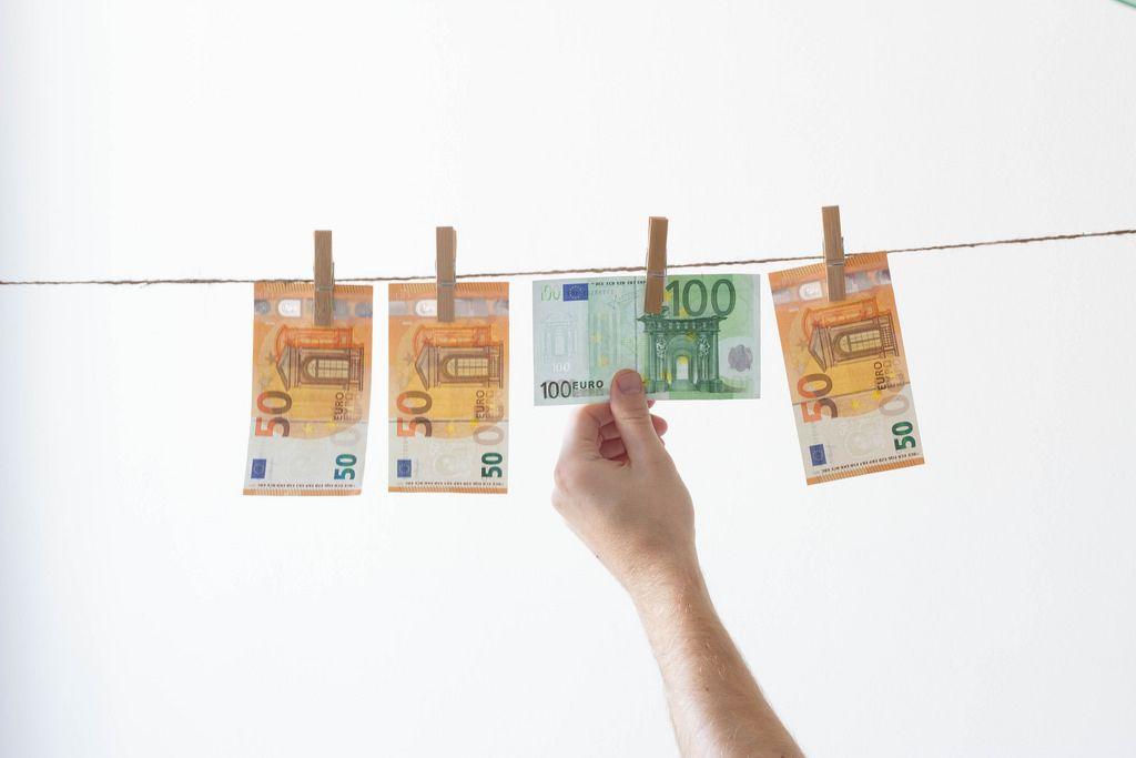 Mann nimmt Geld von Wäscheleine herunter