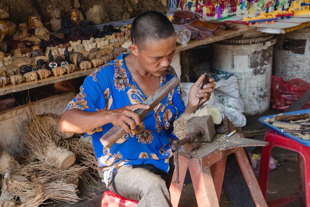 Mann schnitzt eine Holzskulptur und Souvenire auf einer einfachen Werkbank auf einem Markt in Vietnam