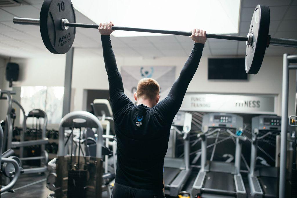 Mann stemmt beim Gewichtheben in Fitnessstudio Langhantel in die Höhe