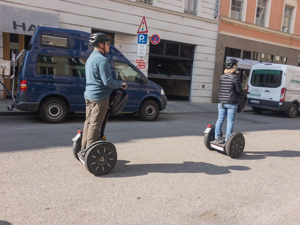 Mann und Frau fahren auf Segways durch die Stadt - München