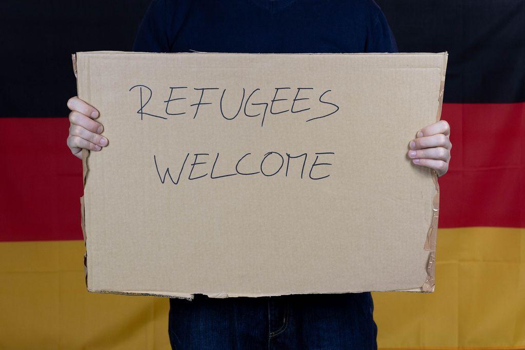 Mann vor deutscher Flagge heißt Flüchtlinge willkommen