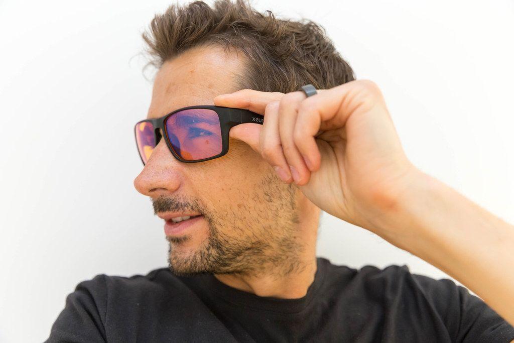 Mann zeigt seine Horus X PC Gaming Brille mit Blaulichtfilter, die die die Augen vor schädlichen Blaulichtstrahlungen schützen