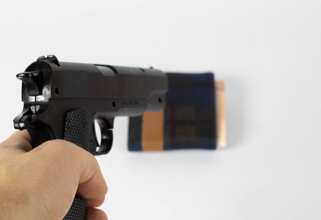 Mann zielt mit der Pistole auf die Brieftasche