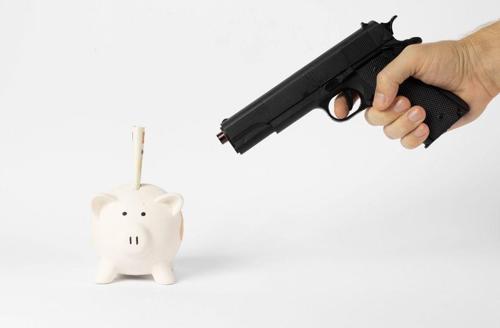 Mann zielt mit Pistole auf Sparschwein