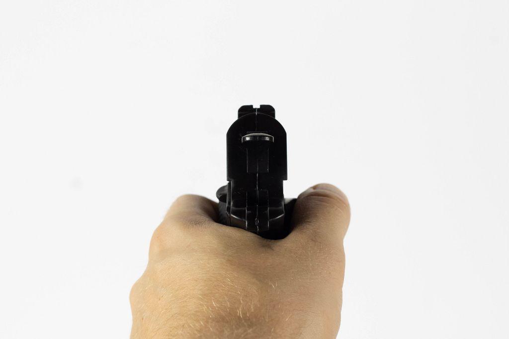 Mann zielt mit seiner Pistole