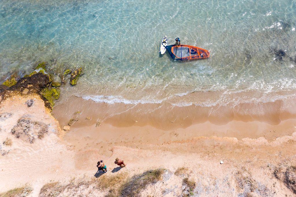 Männer lassen am Santa Maria Strand auf Paros eine Drohne fliegen und machen ein Luftbild von einem Windsurfer, der sein Wassersportgerät abbaut