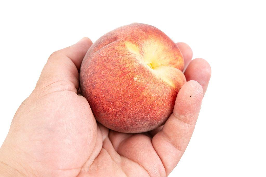 Männerhand hält einen Pfirsich in der Hand