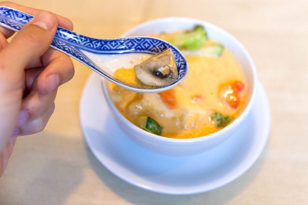 Männerhand löffelt asiatische Kokosmilchsuppe mit Tofu, scharfen Gewürzen und gesundem Gemüse als fleischlose Mahlzeit, in einer Suppenschale