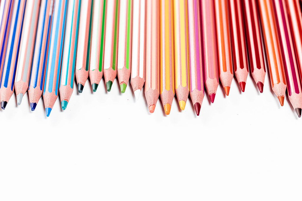 Many colored pencils on the white background with free space