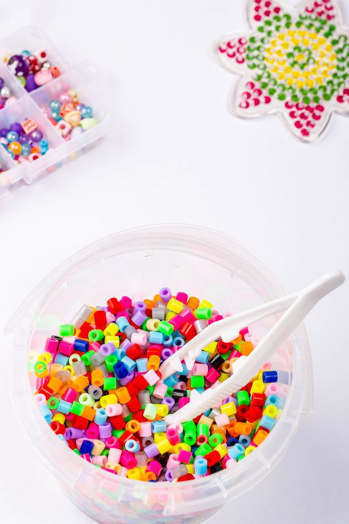 Many little beads with tweezers on white background
