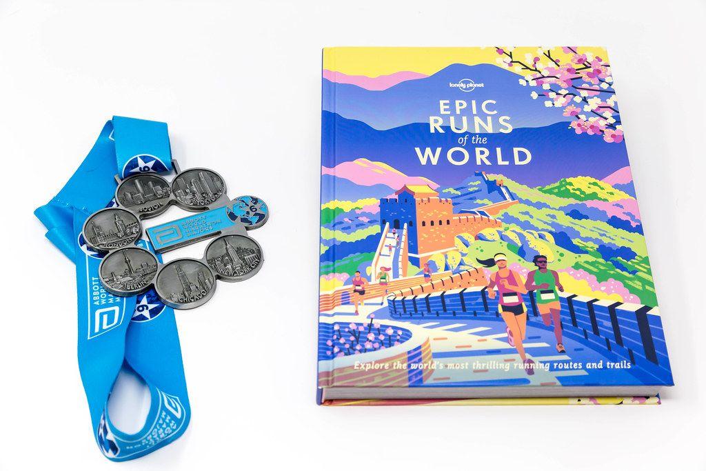 Marathon-Medaillen neben einem Laufstrecken-Buch für Sportler, auf weißer Oberfläche