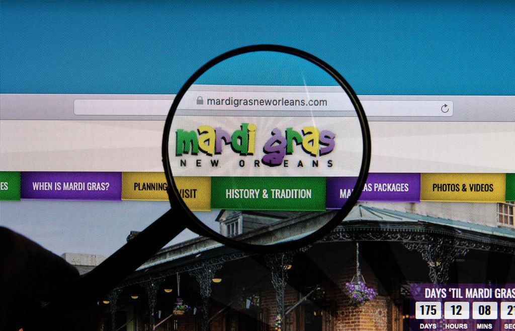 Mardi Gras logo on a computer screen with a magnifying glass