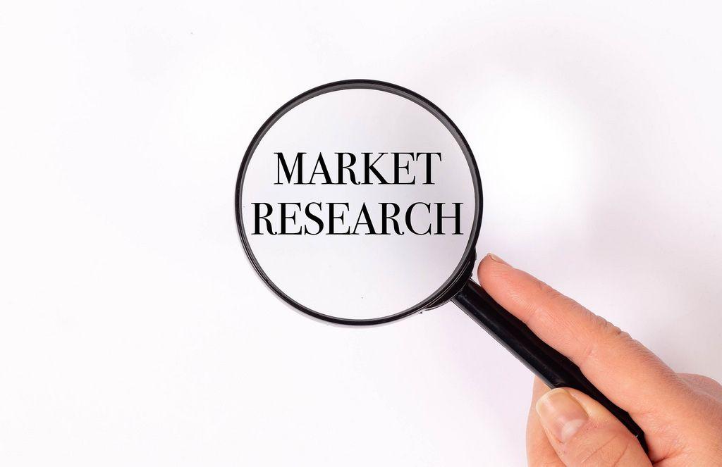 Market research unter der Lupe auf weißem Hintergrund