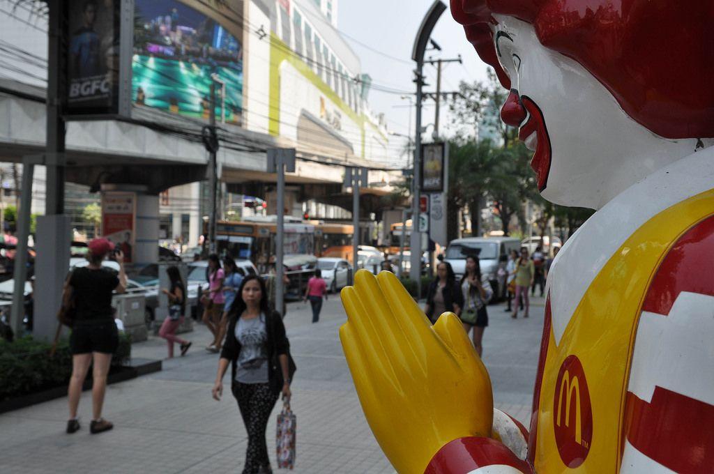 McDonald's Clown mit zusammengelegten Händen und Passanten im Hintergrund