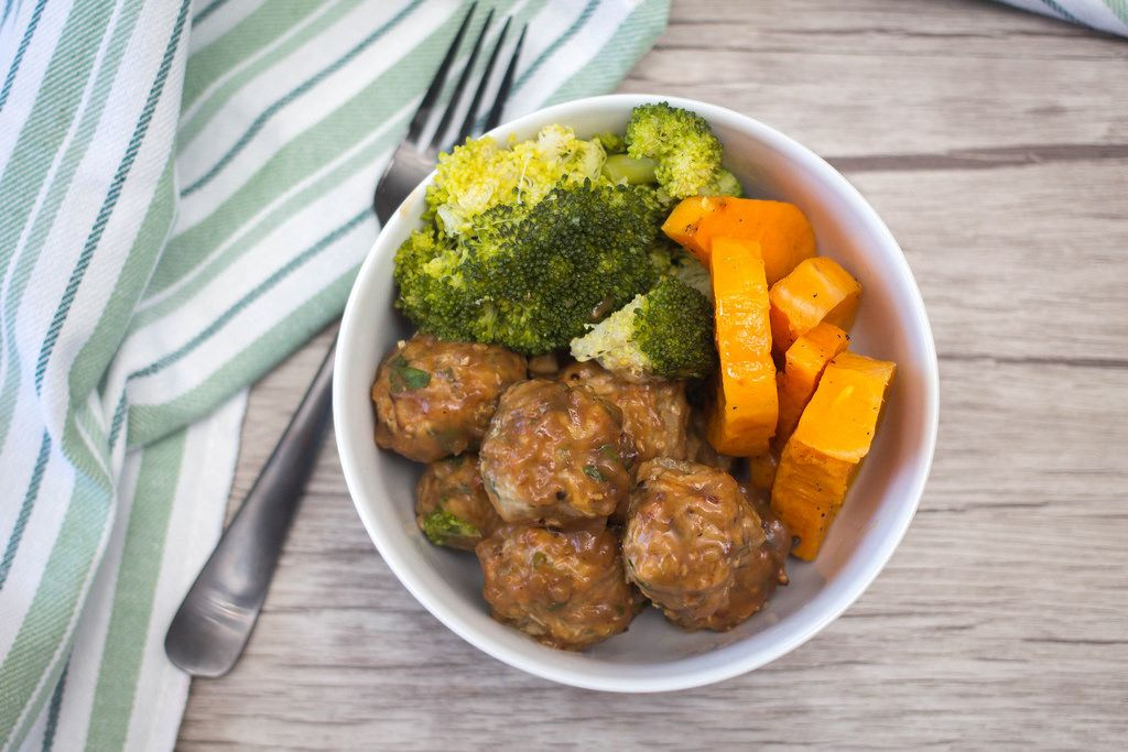 Meatballs with sauce, broccoli and pumpkin in a bowl on a table with fork and kitchen towel aside