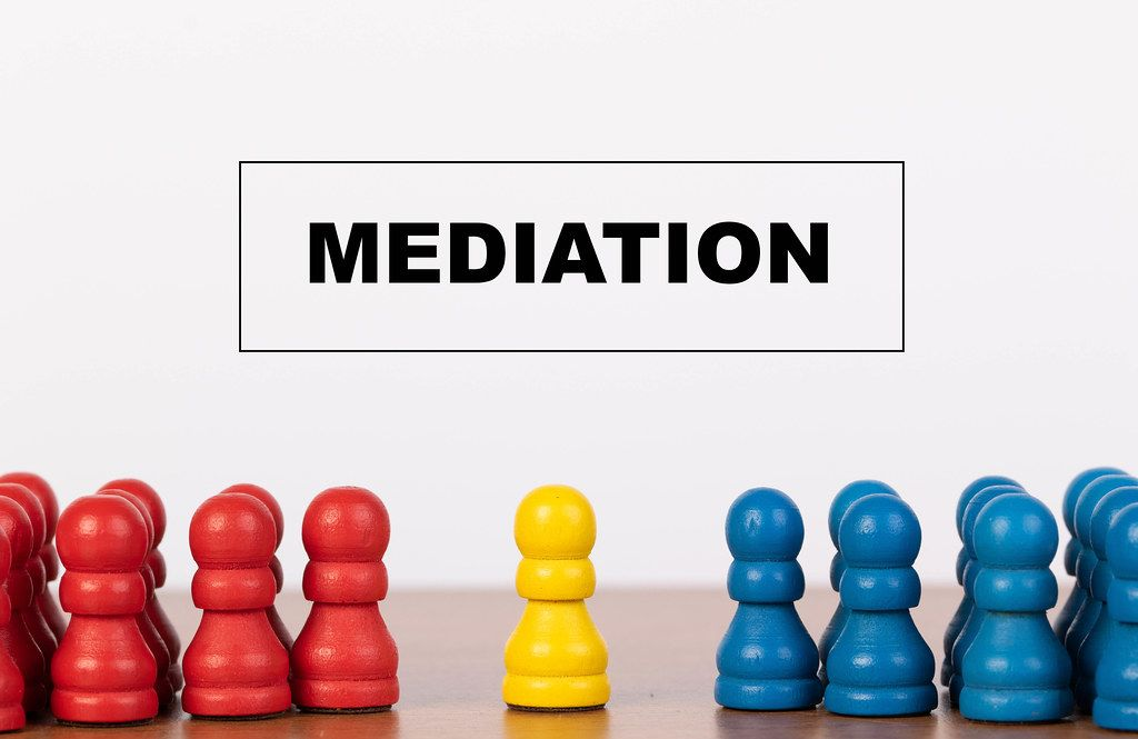 Mediation concept with pawn figurines on table