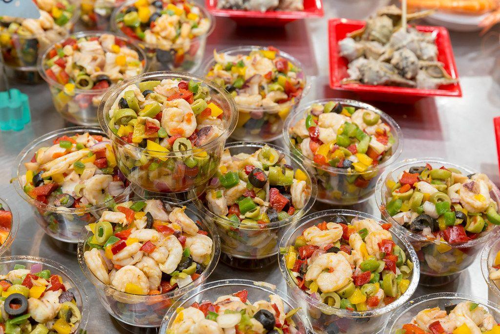 Mediterraner Salat mit Shrimps, Oliven und frischem Gemüse, wird als Fertigessen in der Mercat de la Boqueria Markthalle in Barcelona (Spanien) verkauft