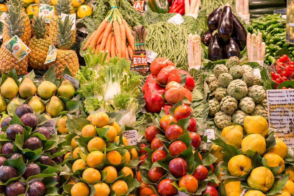 Mediterranes Obst & Gemüse wie Cherimoya, Spargel, Ananas, Fenchel und Auberginen in der Mercat de la Boqueria in Barcelona, Spanien