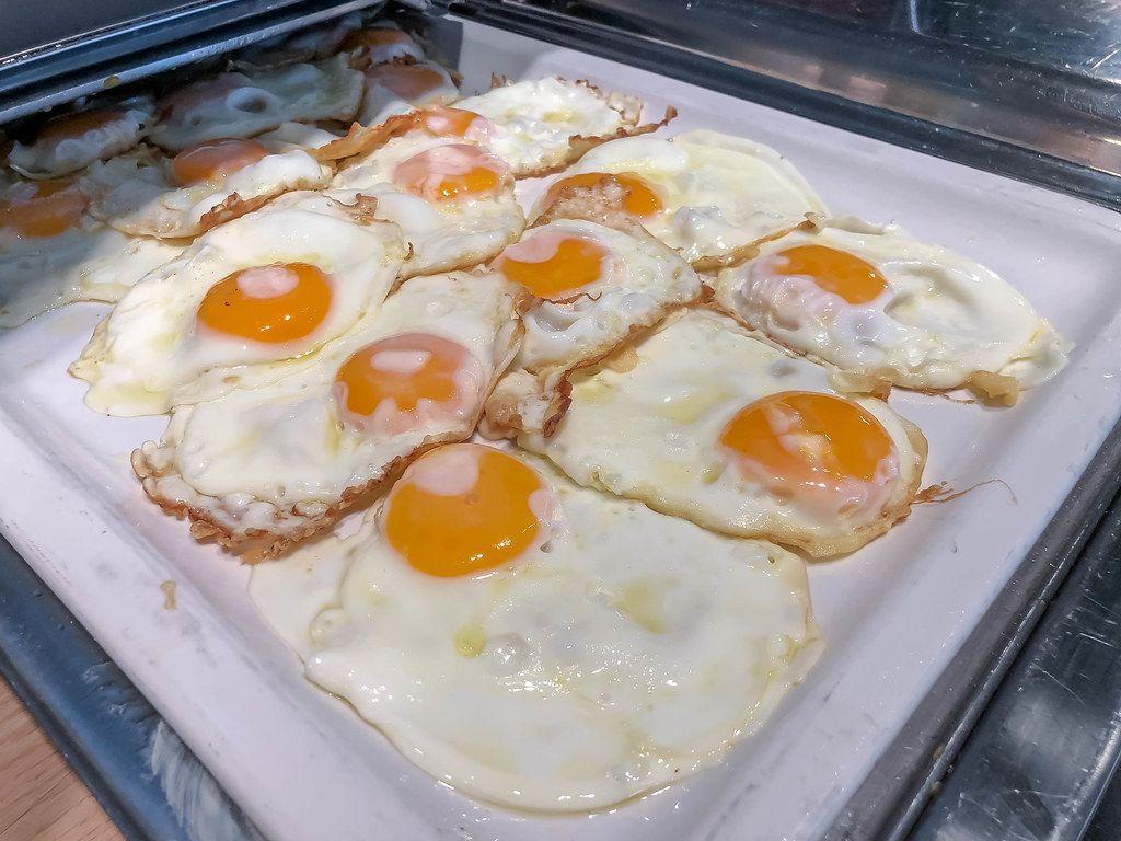 Mehrere Spiegeleier auf einem Wärmetablett am Frühstücksbüfett