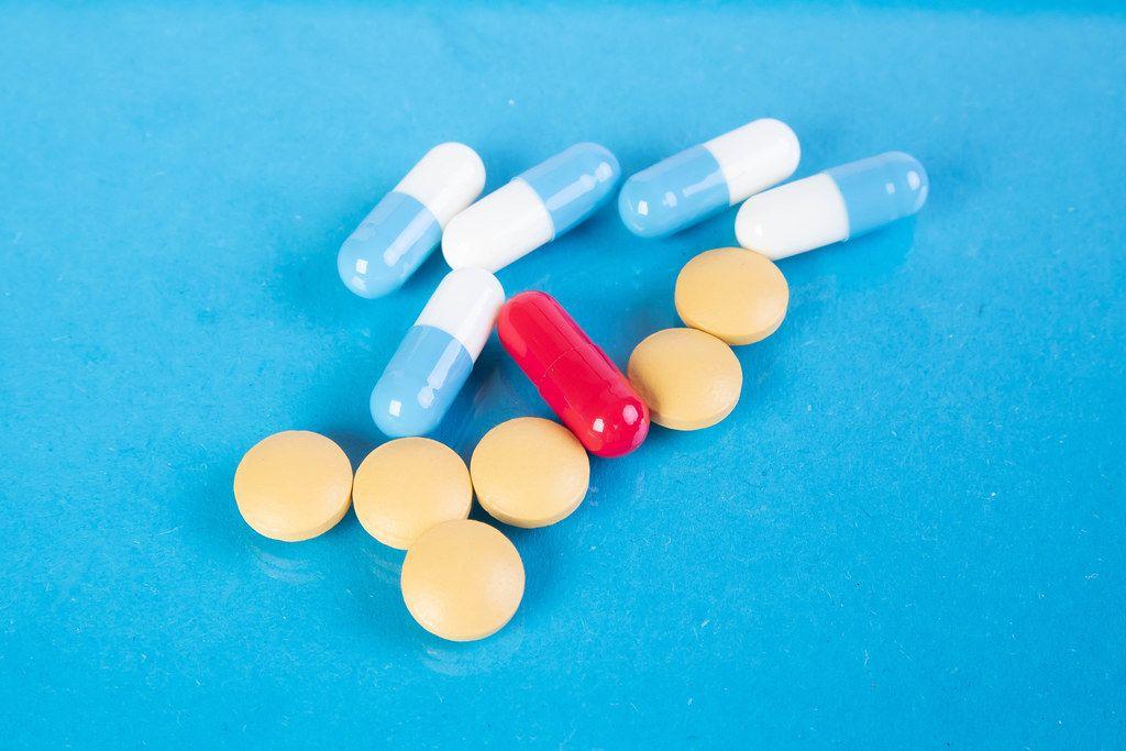 Mehrere Tabletten und Kapseln auf einer blauen Oberfläche