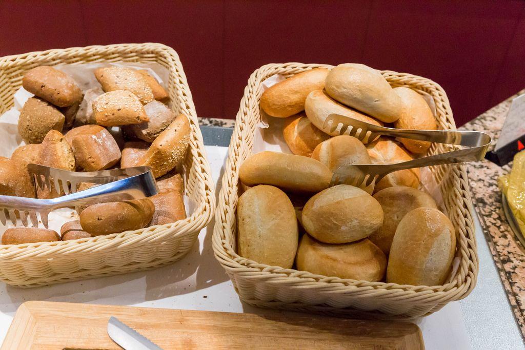 Mehrkornbrötchen und Baguette-Brötchen in Brotkörben