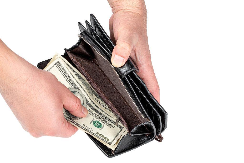 Men's hands put money in the wallet