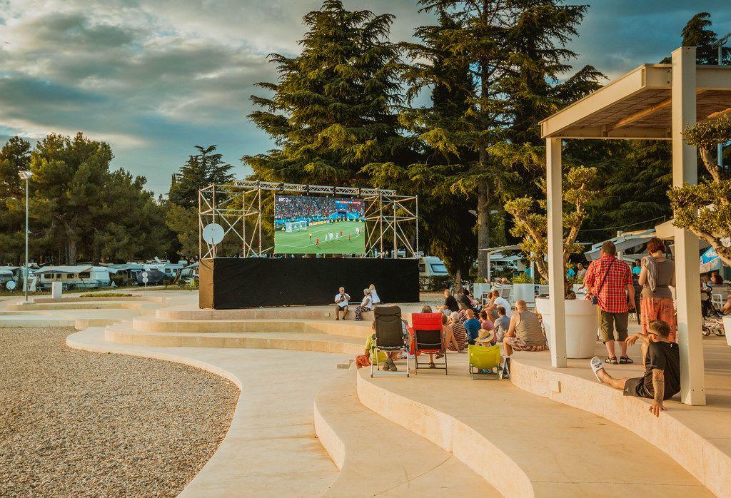 Menschen schauen Fußballspiel auf Großbildleinwand unter freiem Himmel