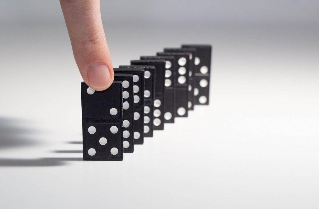 Menschliche Hand dabei eine Reihe von Dominosteinen zum Sturz zu bringen