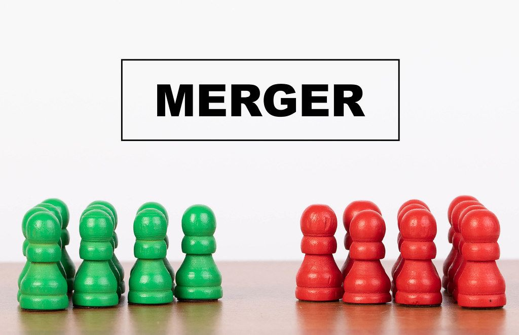 Merger concept with pawn figurines on table