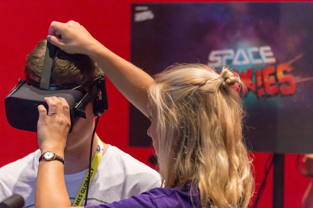 Messehostess hilft einem Besucher beim Aufsetzen des VR Headsets