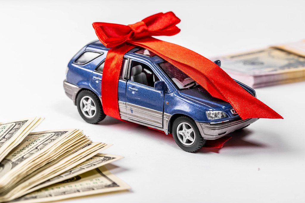 Metal car model with bow and red gift ribbon on white background with dollars (Flip 2019)