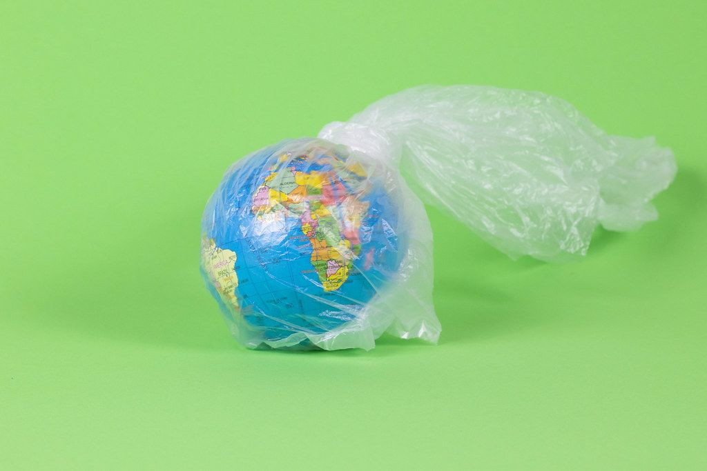 Miniature Globe wrapped in a single use Plastic Bag with Green Background