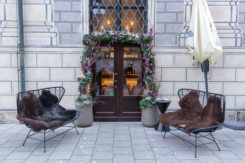 Mit Fell ausgestattete Sitzbänke vor mit Blumen dekortiertem Restauranteingang
