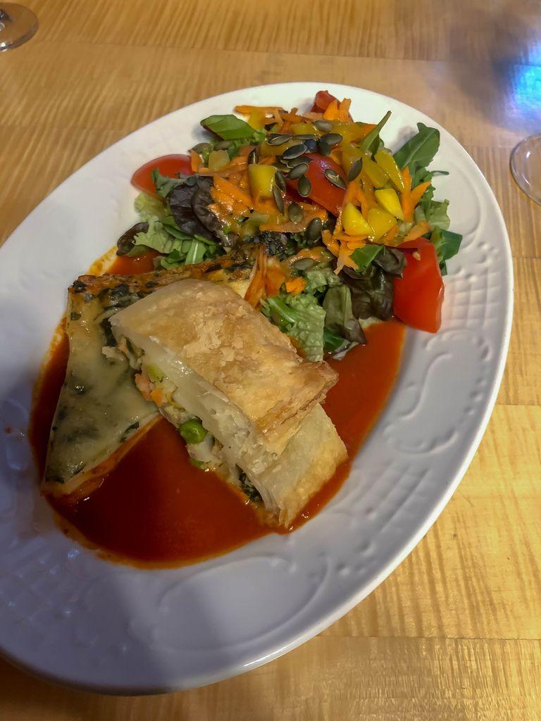 Mit Gemüse und Salat angerichtete Gemüselasagne in Tomatensoße auf Holztisch