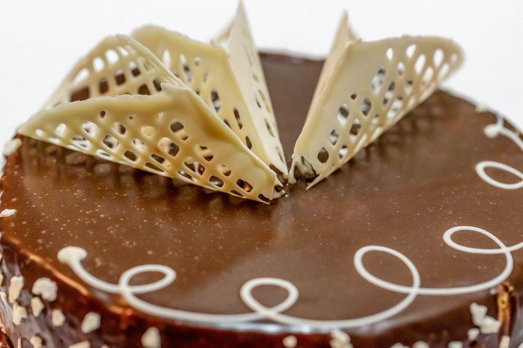 Mit Schokoladenguss überzogener Kuchen, verziert mit gehackten Nüssen und Dekoration aus weißer Schokolade