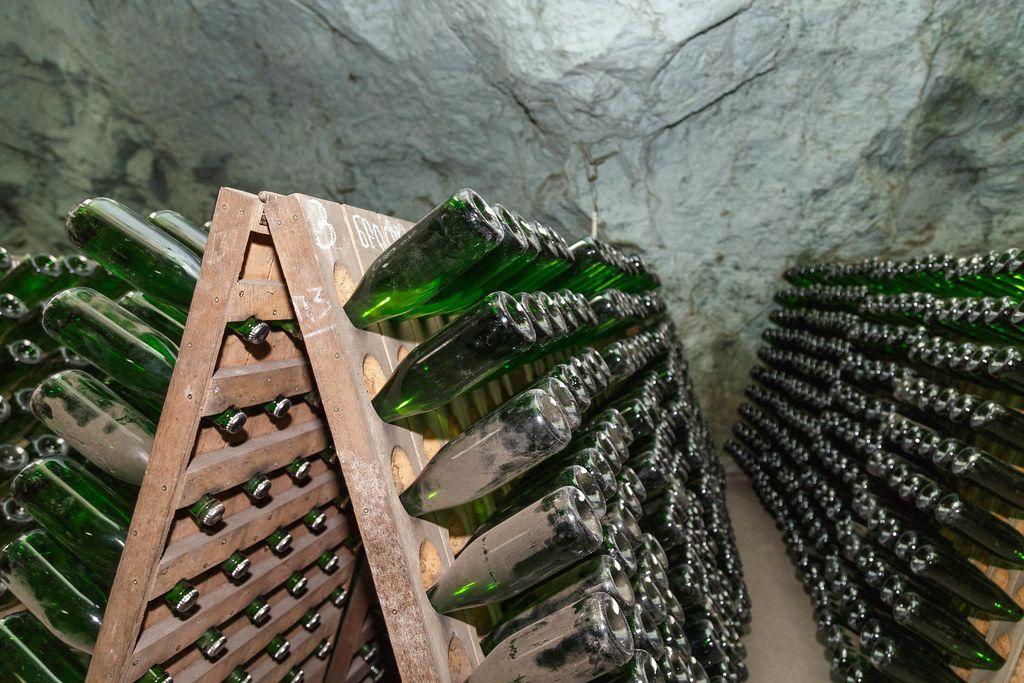 Mit Staub überzogene Champagnerflaschen bei der Alterung in speziellen Holzregalen in einem Gewölbekeller