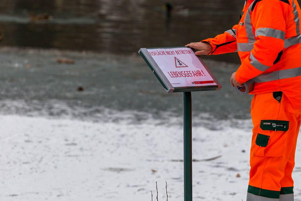 Mitarbeiter der Stadt Köln bringt Schild am Decksteiner Weiher an