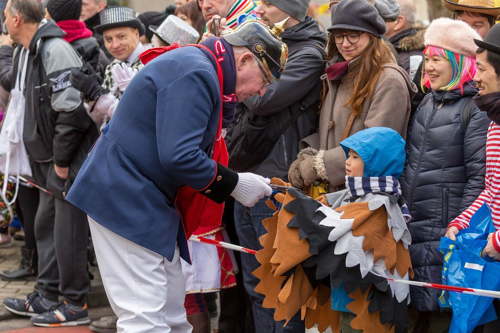 Mitglied der Kölsche Funkentöter von 1932 gibt einem Jungen ein Geschenk - Kölner Karneval 2018