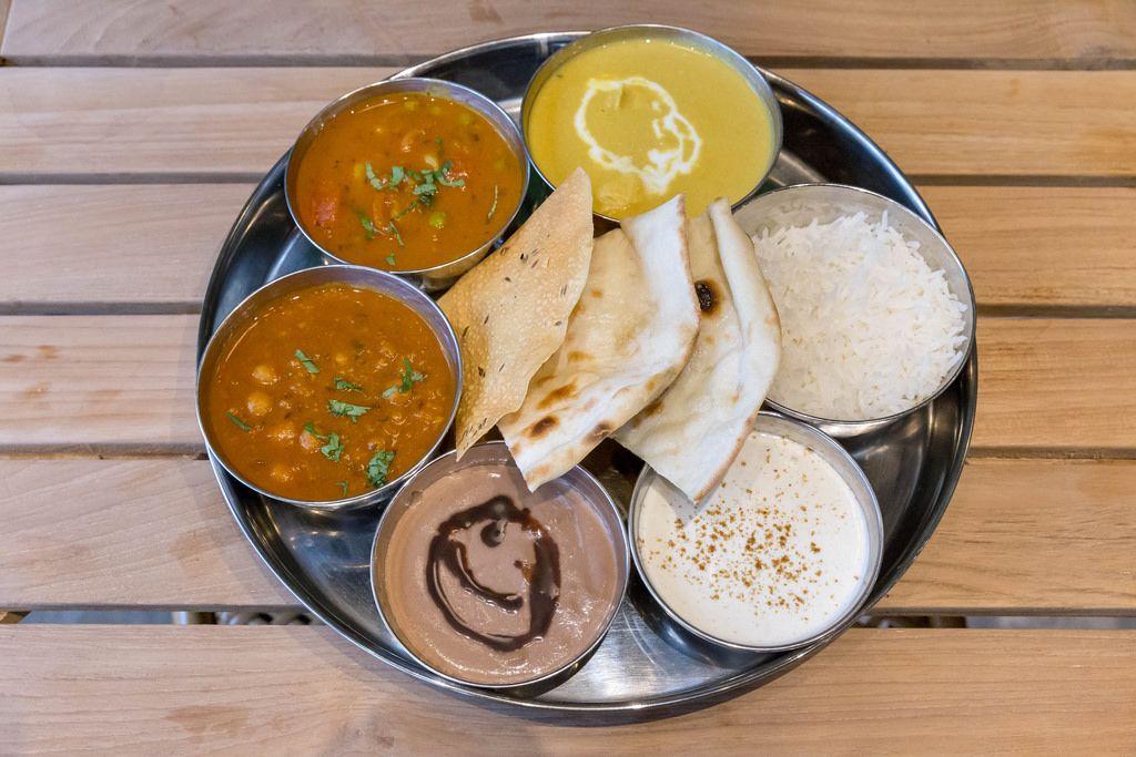 Mittagessen in einem indischen Restaurant, Schälchen mit Curry werden mit Reis und Fladenbrot serviert
