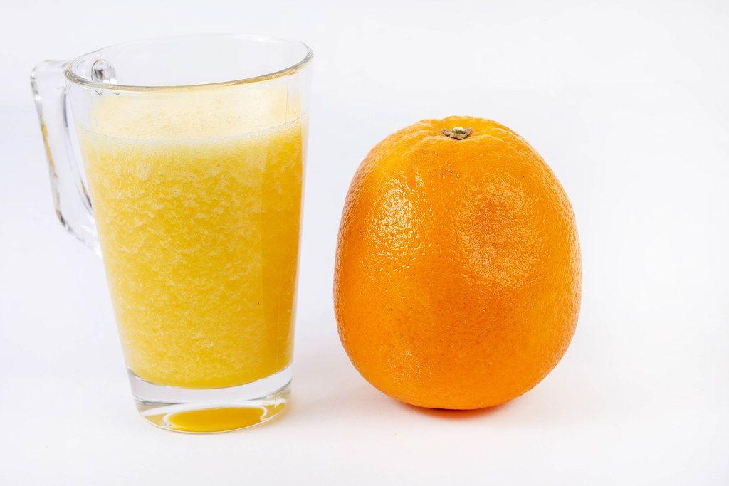 Mixed Orange juice with whole Orange on the white table (Flip 2019)