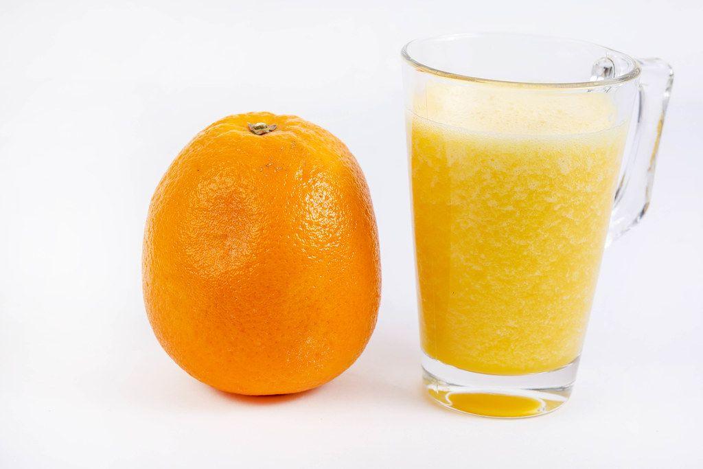 Mixed Orange juice with whole Orange on the white table