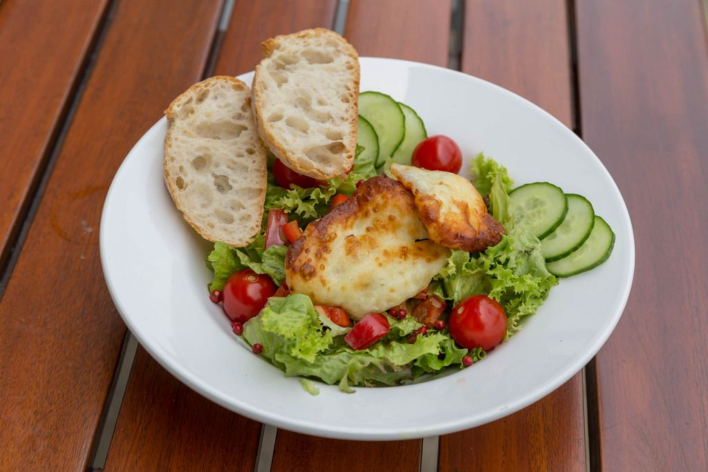 Mixed salad with cucumber, cherry tomato, halloumi cheese and two slices of bread