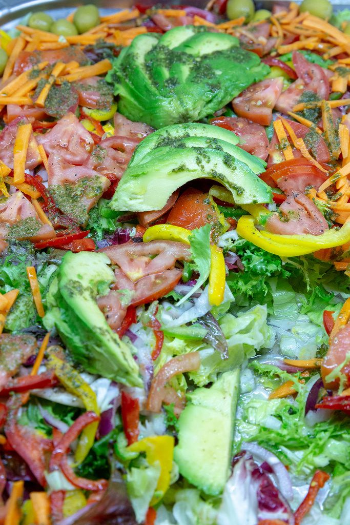 Mixed salad with tomatoes, colorful peppers and avocado on top