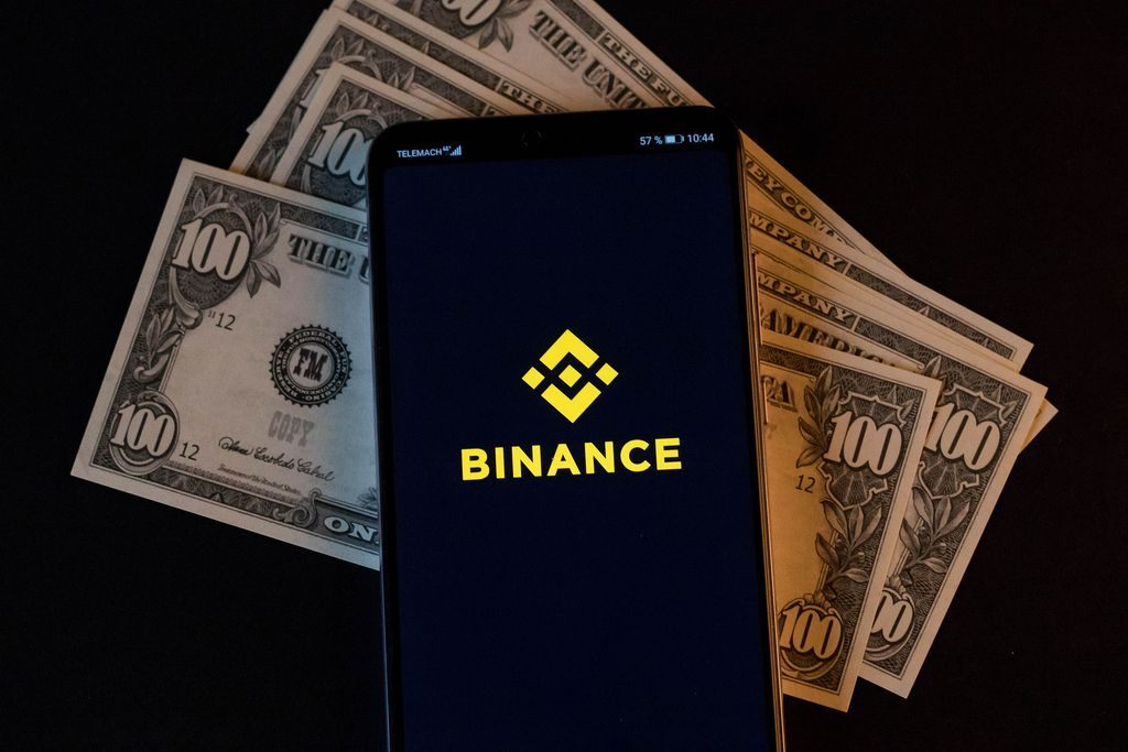 Mobile phone and Binance logo on dollars